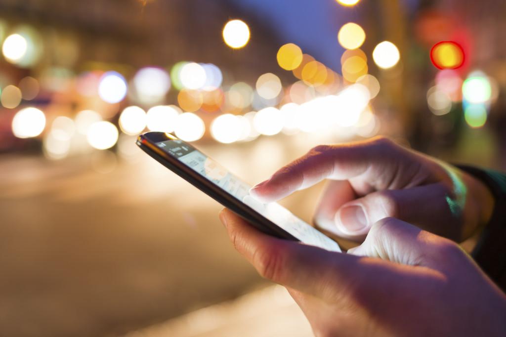 Man using his Mobile Phone in the street, night light bokeh Back