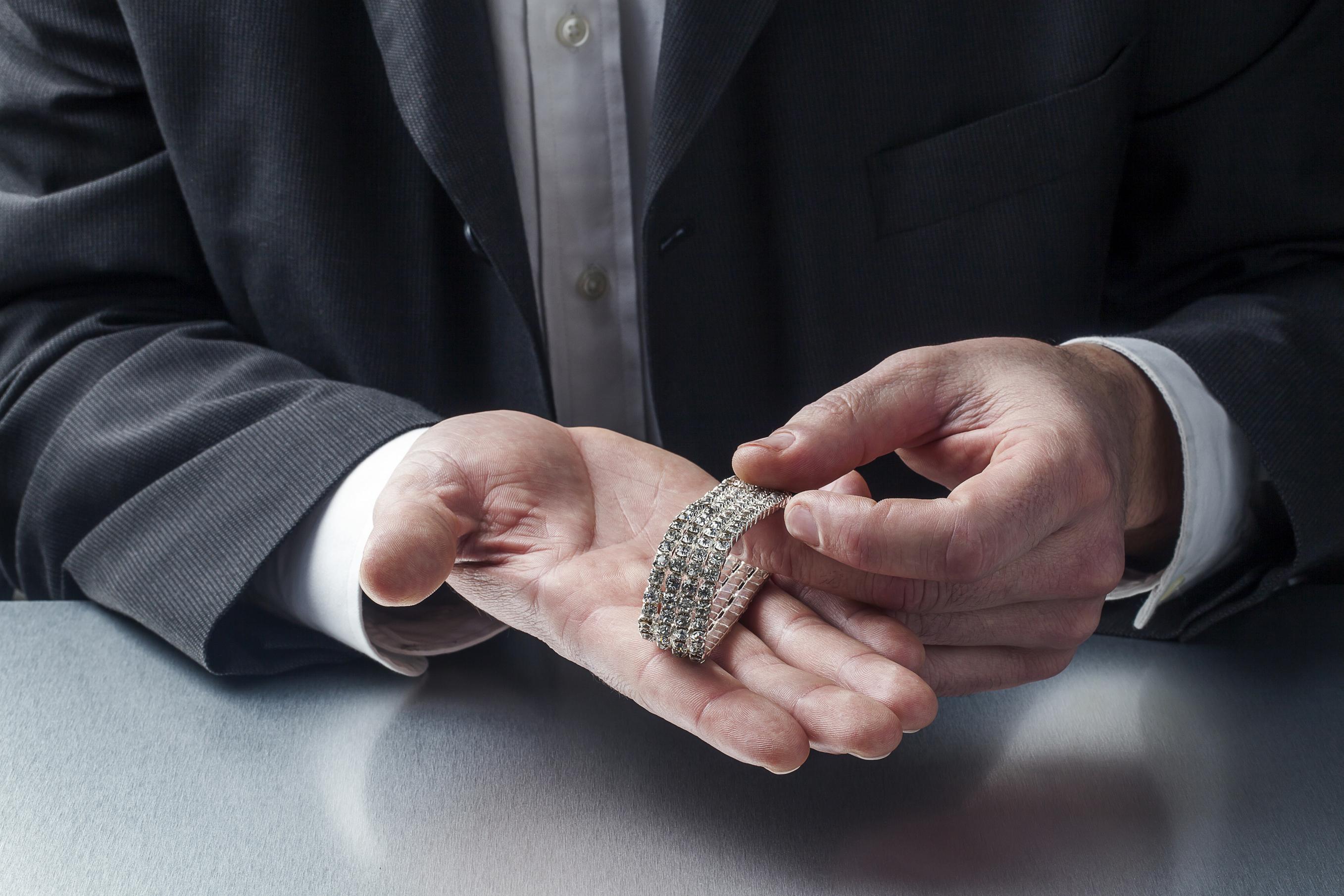 male appraiser's hands holding sparkling bracelet in hands